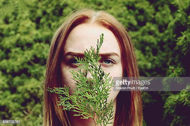 Portrait Of Young Woman Covering Face With Plant Against Trees