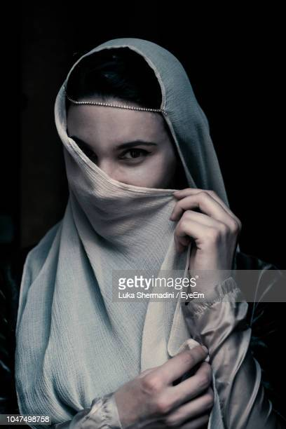 Portrait Of Young Woman Covering Face With Scarf Against Black Background