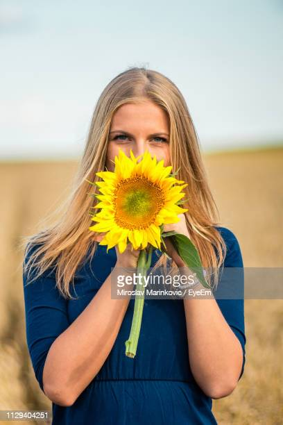 portrait of young woman covering mouth with sunflower against sky - long stem flowers stock pictures, royalty-free photos & images