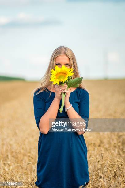 portrait of young woman covering mouth with sunflower on wheat field against sky - long stem flowers stock pictures, royalty-free photos & images