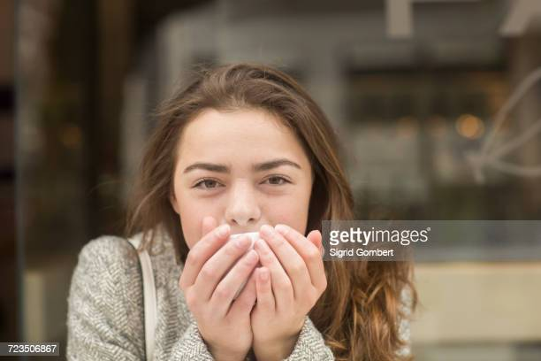 portrait of young woman cupping coffee at sidewalk cafe - sigrid gombert stock pictures, royalty-free photos & images