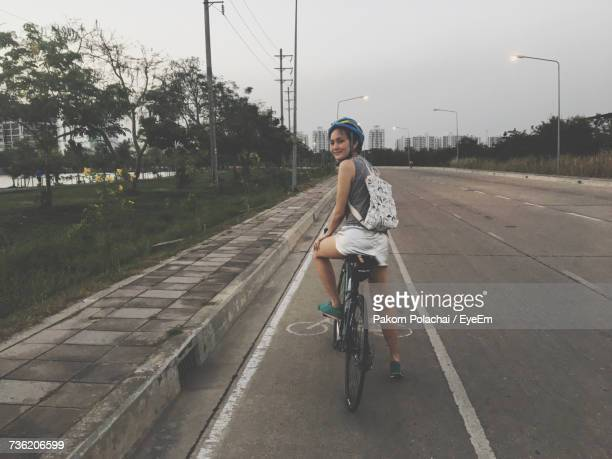 Portrait Of Young Woman Cycling On Street In City Against Sky