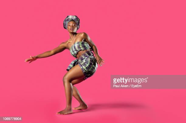 portrait of young woman dancing against pink background - aikāne stock pictures, royalty-free photos & images