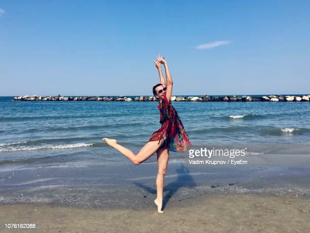 Portrait Of Young Woman Dancing At Beach Against Blue Sky