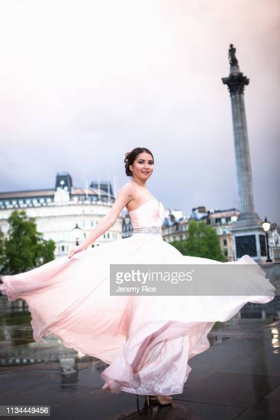 portrait of young woman dancing in evening gown at dusk, trafalgar square, london, uk - ダンス ドレス ストックフォトと画像