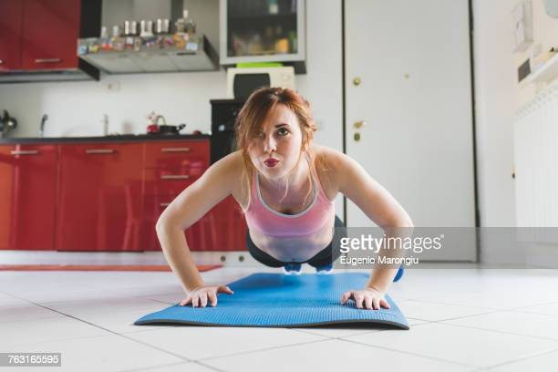 portrait of young woman doing push ups on kitchen floor - home workout stock pictures, royalty-free photos & images