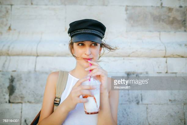 portrait of young woman drinking a smoothie - milkshake imagens e fotografias de stock