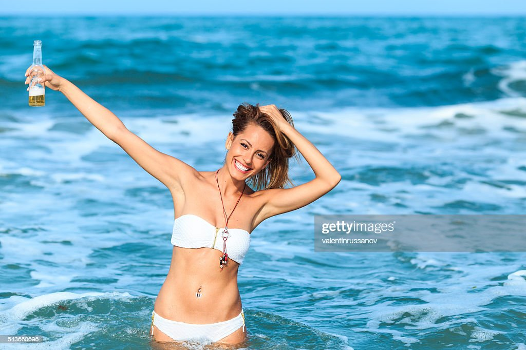 Portrait of young woman drinking beer in the sea