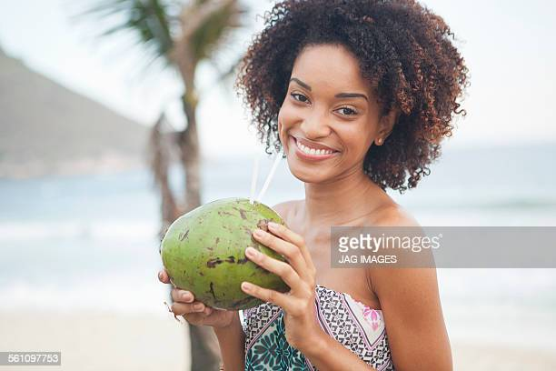 Portrait of young woman drinking coconut milk at beach, Rio De Janeiro, Brazil