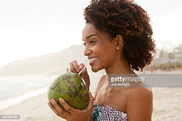 Portrait of young woman drinking coconut milk on beach, Rio De Janeiro, Brazil