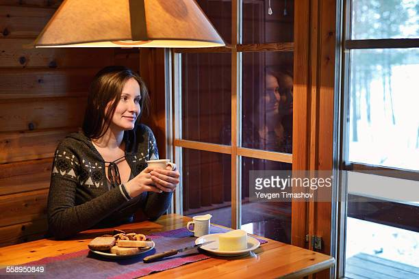 Portrait of young woman drinking coffee and looking out of window, Posio, Lapland, Finland
