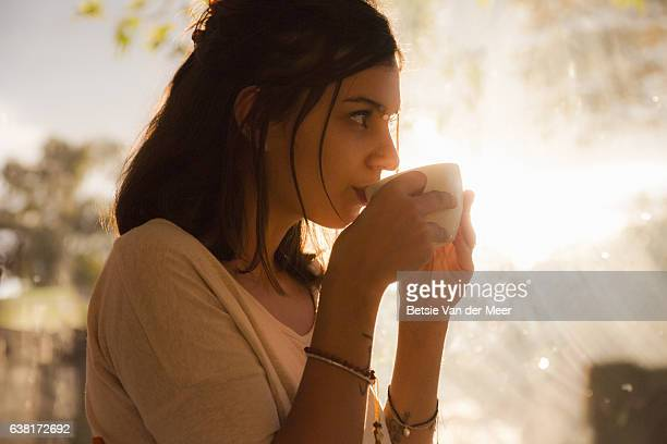 Portrait of young woman drinking coffee, with sunlight shining through the window.