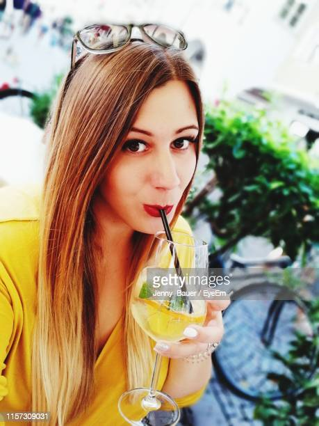 portrait of young woman drinking drink in glass - only young women stock pictures, royalty-free photos & images