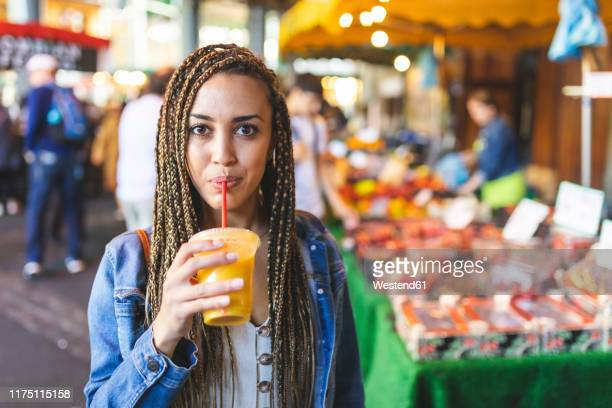 portrait of young woman drinking fresh orange juice on street market, london, uk - young women stock pictures, royalty-free photos & images