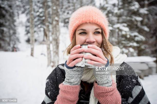 portrait of young woman drinking hot drink outdoors in winter - warm clothing stock pictures, royalty-free photos & images
