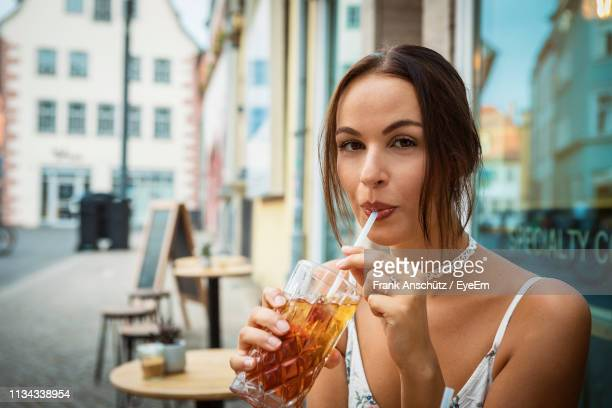 portrait of young woman drinking ice tea from glass at restaurant - thuringia stock pictures, royalty-free photos & images