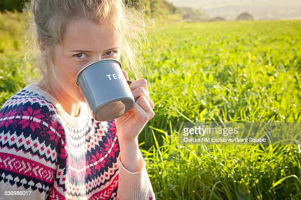 Portrait of young woman drinking tea in rural field