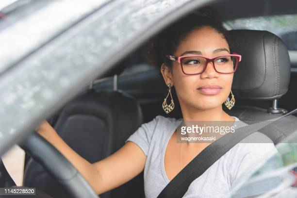 portrait of young woman driving a car - driver stock pictures, royalty-free photos & images