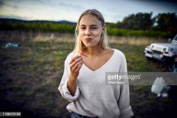 portrait of young woman eating a carrot in the countryside - vergnügen stock-fotos und bilder