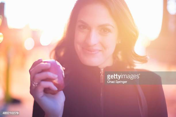 Portrait of young woman eating an apple on the street