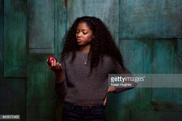 portrait of young woman eating an apple - afro amerikaanse etniciteit stockfoto's en -beelden