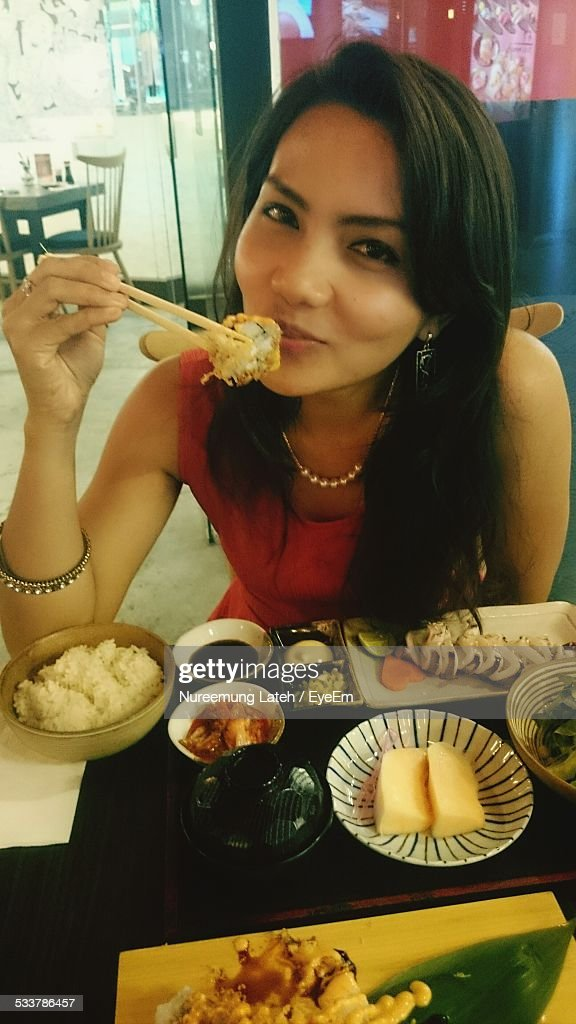 Portrait Of Young Woman Eating Asian Food : Foto stock