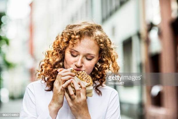 portrait of young woman eating bagel outdoors - vergnügen stock-fotos und bilder