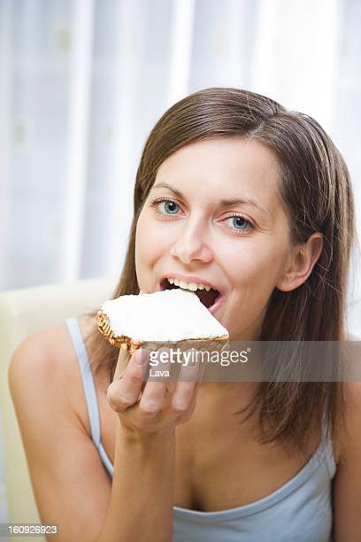 portrait of young woman eating bread