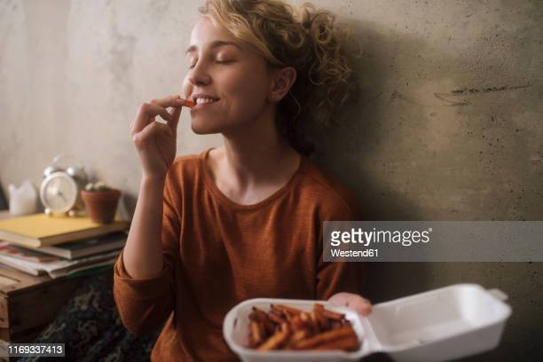 portrait of young woman eating french fries at home - vergnügen stock-fotos und bilder