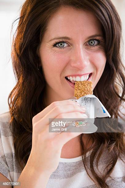 Portrait of young woman eating granola bar