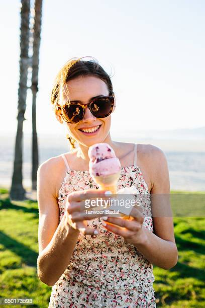 Portrait of young woman eating ice cream cone at coast, Venice Beach, California, USA