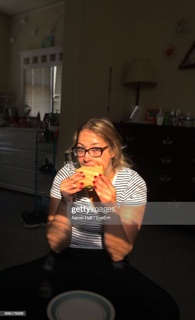 Portrait Of Young Woman Eating Sandwich At Home : Stock Photo