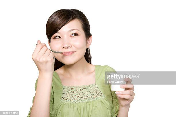 Portrait of Young Woman Eating Yogurt