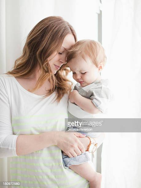 portrait of young woman embracing baby boy (6-11 months) - 6 11 months stock pictures, royalty-free photos & images