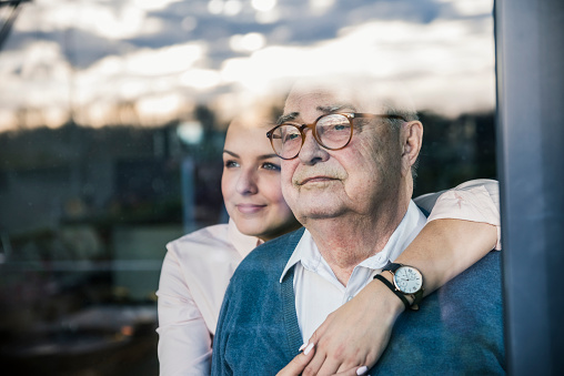 Portrait of young woman embracing senior man at the window - gettyimageskorea