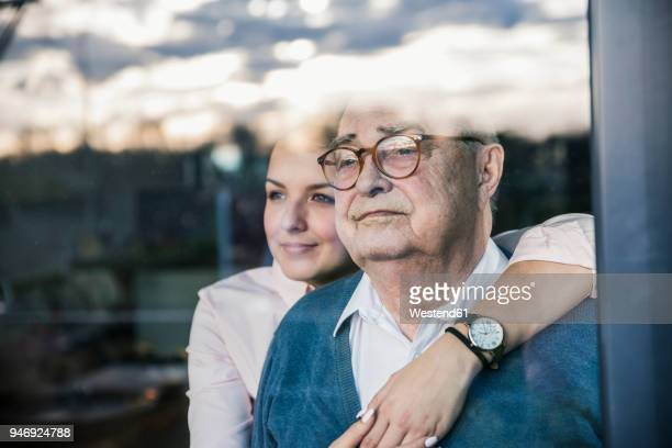 portrait of young woman embracing senior man at the window - alter erwachsener stock-fotos und bilder