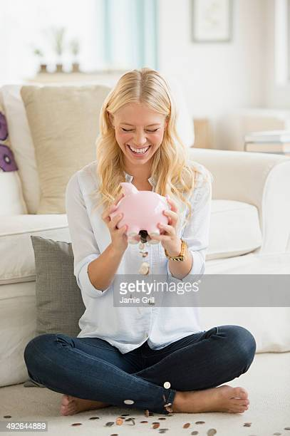 Portrait of young woman empting coins from piggy bank, Jersey City, New Jersey, USA