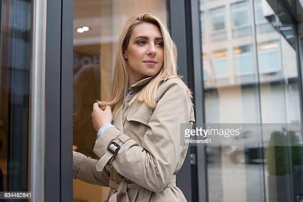 Portrait of young woman entering a shop