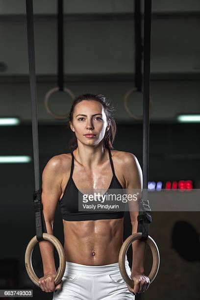 portrait of young woman exercising on gymnastic rings at gym - frauen ringen stock-fotos und bilder