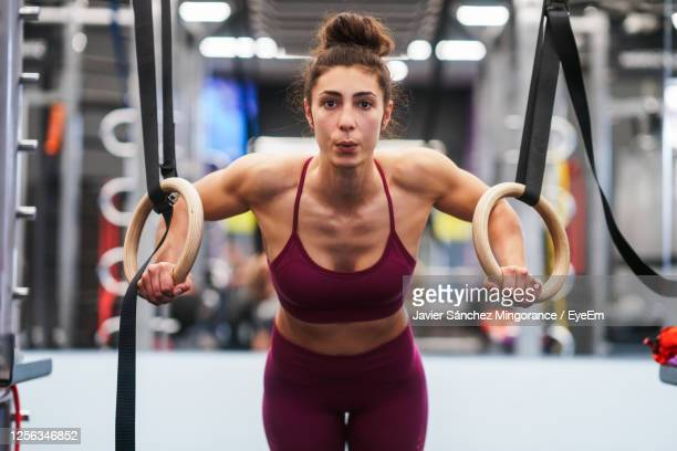 portrait of young woman exercising on gymnastics rings - gymnastics poses stock pictures, royalty-free photos & images