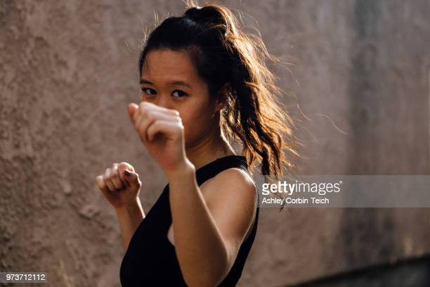 portrait of young woman exercising outdoors, in fighting stance - fighting stance stock pictures, royalty-free photos & images