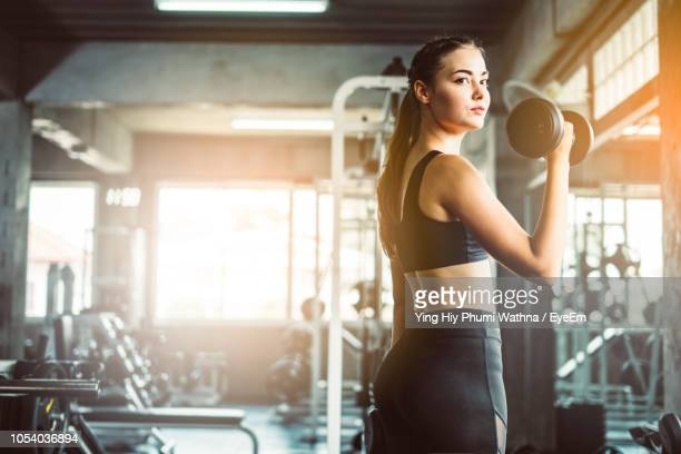 portrait of young woman exercising with dumbbells in gym - fitnesseinrichtung stock-fotos und bilder