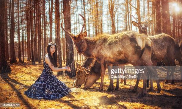 Portrait Of Young Woman Feeding Animals In Forest
