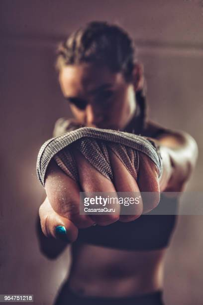 Portrait of Young Woman Fighter Punching Towards Camera