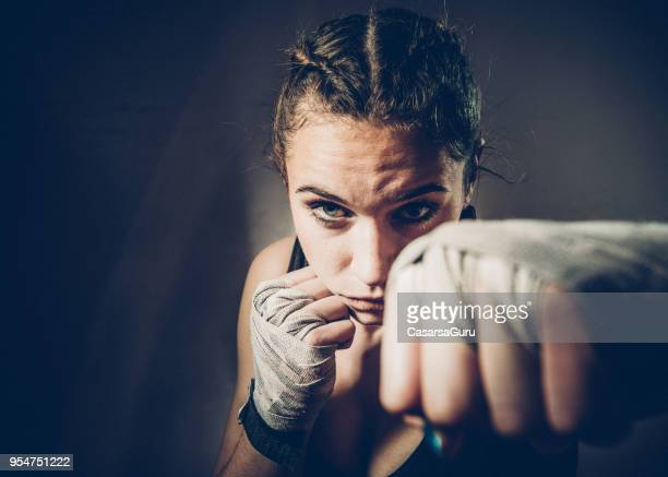 portrait of young woman fighter punching towards camera - combat sport stock pictures, royalty-free photos & images