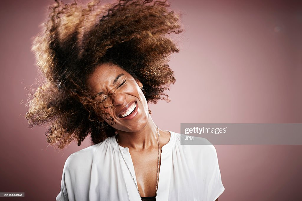 Portrait of young woman flicking hair, smiling : Stock Photo