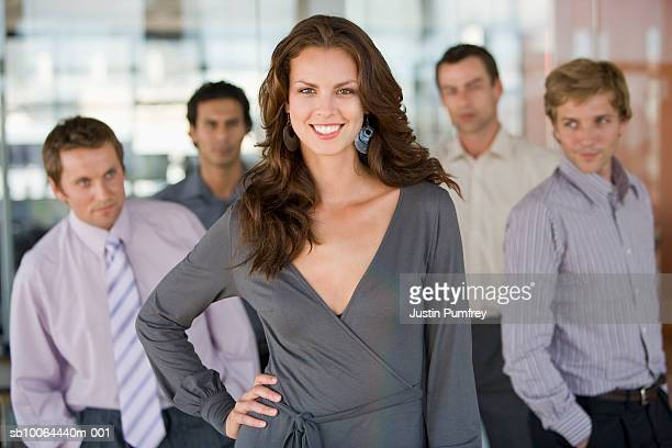 portrait of young woman, four men in background looking at her - adulation stock pictures, royalty-free photos & images