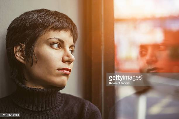 portrait of young woman gazing out of window at the street - staring stock photos and pictures
