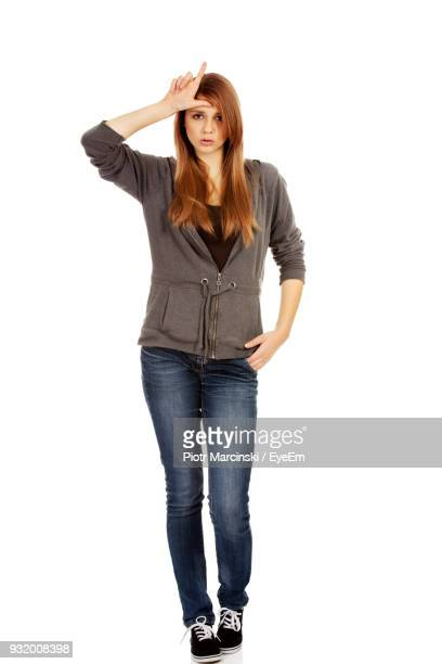 portrait of young woman gesturing against white background - teasing stock pictures, royalty-free photos & images