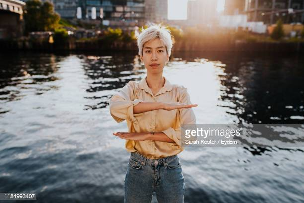 portrait of young woman gesturing equal sign while standing against lake in city - gleichheit stock-fotos und bilder